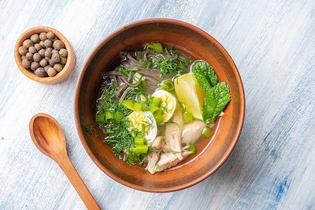 Vista dall'alto gustosa zuppa imperiale vietnamita con limone, menta, erbe e pasta di grano saraceno, pesce. ciotola con zuppa per pranzo su sfondo blu.
