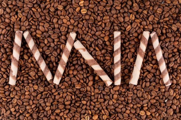 Vista dall'alto gustosi rotoli di wafer sulla superficie dei chicchi di caffè