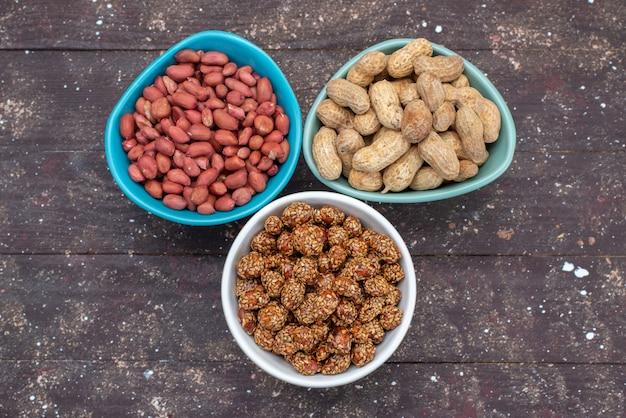 Vista dall'alto i dadi all'interno dei piatti diversi tipi di noci sulla foto dello spuntino delle arachidi del dado dello scrittorio di legno