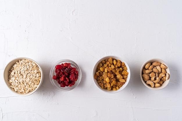 Vista dall'alto il set di superfoods in ciotole su sfondo bianco e copia spazio.