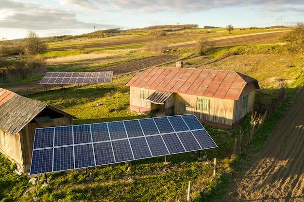 Vista dall'alto in basso aerea dei pannelli solari nell'iarda verde del villaggio rurale
