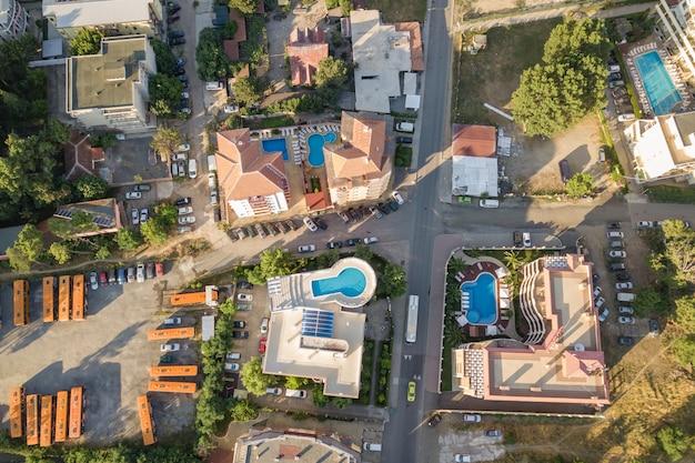Vista dall'alto in basso dei tetti degli hotel, strade con auto parcheggiate e piscine con acqua blu nella località turistica vicino al mare.