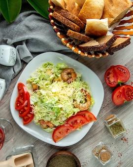 Vista dall'alto insalata caesar con fette di pomodoro gamberetti e un bicchiere di bibita