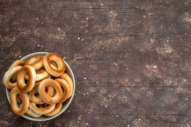 Vista dall'alto intorno gustosi cracker dolce e secco all'interno del piatto su marrone, cracker dolce patatine biscotto