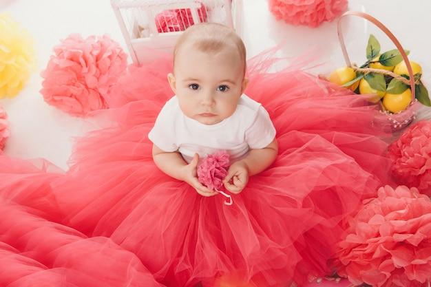 Vista dall'alto: la bambina madre seduta in abiti rosa sul pavimento