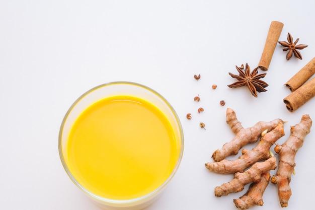Vista dall'alto latte di curcuma di latte dorato su sfondo bianco con radici e spezie di curcuma