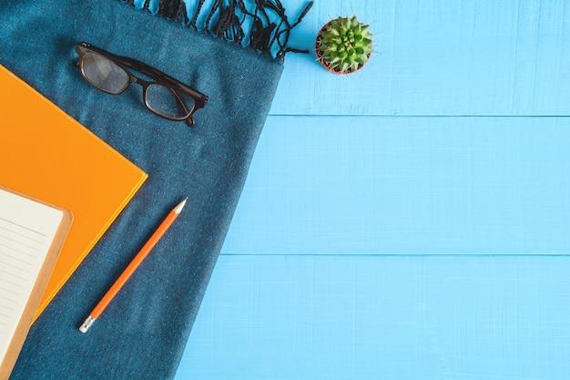 Vista dall'alto libro e matita nota sul tavolo di legno blu