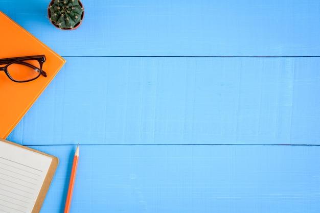 Vista dall'alto libro mockup e matita nota sul tavolo di legno blu