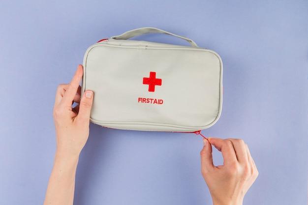 Vista dall'alto mani che tengono il kit di pronto soccorso