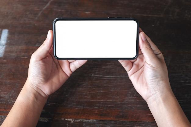 Vista dall'alto mani che tengono il telefono cellulare nero con lo schermo del desktop vuoto orizzontalmente sul fondo della tavola in legno