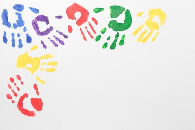 Vista dall'alto mani colorate su sfondo bianco con copia spazio