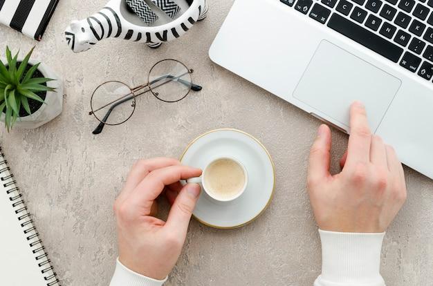 Vista dall'alto mani con caffè e laptop