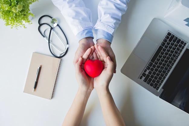 Vista dall'alto . mani del paziente e di medico che tengono cuore rosso sulla tavola bianca