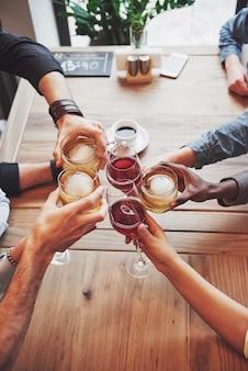 Vista dall'alto. mani di persone con bicchieri di whisky o di vino, celebrando e brindando in onore del matrimonio o altra celebrazione