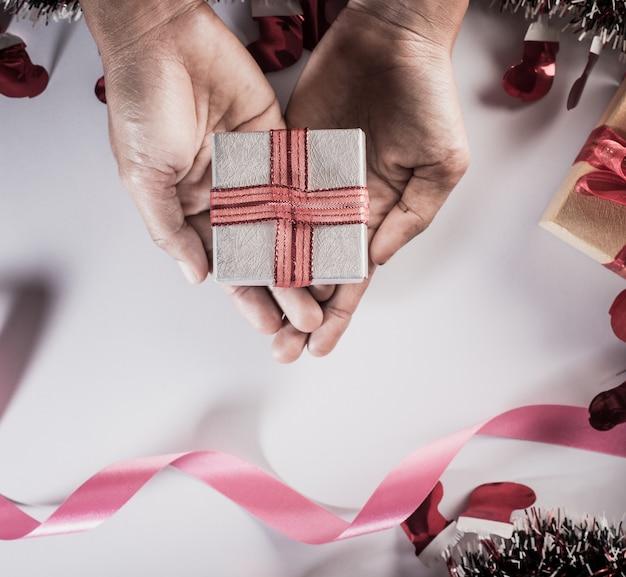 Vista dall'alto mano che tiene confezione regalo nello spazio di lavoro