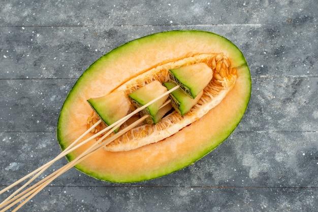 Vista dall'alto melone su bastoncini verdi e succosa morbida foderata su grigio, parte melone di frutta