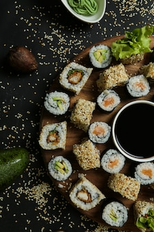 Vista dall'alto mescolare rotoli con salsa di soia su un supporto con semi di sesamo avocado riso allo zenzero e wasabi