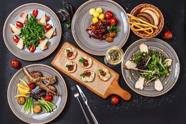 Vista dall'alto mix di fast food carne di agnello alla griglia cetriolo pomodoro patatine fritte insalata di rucola con salmone e parmigiano petto di pollo grigliato con verdure fresche pane bas