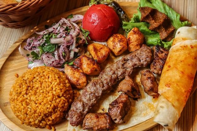 Vista dall'alto mix di kebab con cipolla di bulgur e pane pita con verdure su un supporto