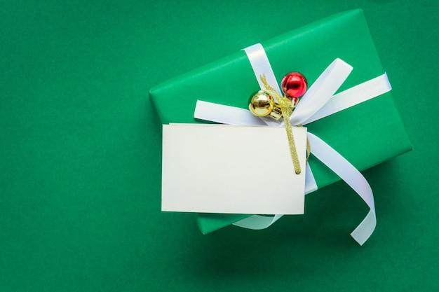 Vista dall'alto mock up etichetta di testo bianco e scatole regalo sul tavolo verde