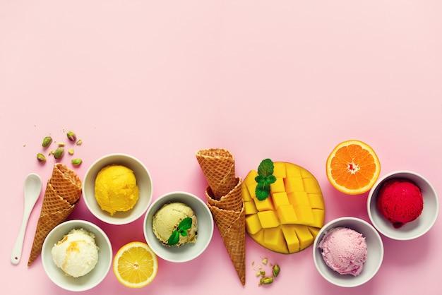 Vista dall'alto palle rosse, viola, gialle, verdi, gelato in ciotole, coni di cialda, bacche, arancia, mango, pistacchio, rosa shabby chic.