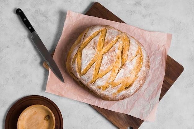 Vista dall'alto pane rotondo con coltello su carta da forno
