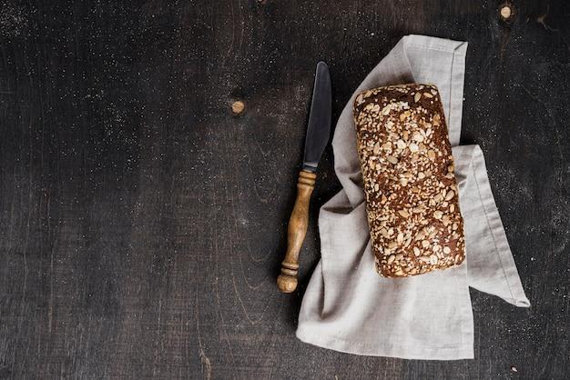 Vista dall'alto pane saporito su stoffa e coltello