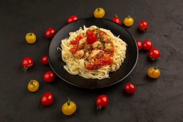 Vista dall'alto pasta cotta con pezzi di pollo e salsa di pomodoro all'interno della piastra nera sul buio