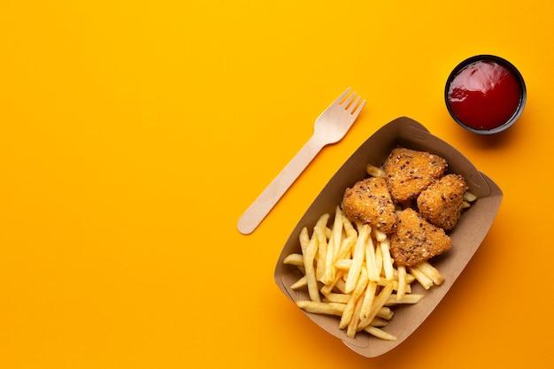 Vista dall'alto patatine fritte e croccanti in una scatola con salsa