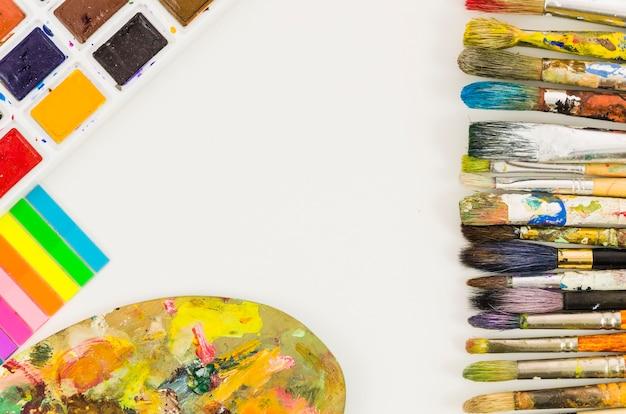 Vista dall'alto pennelli sporchi linea con tavolozza e acquerelli