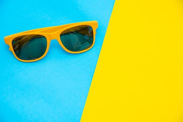 Vista dall'alto per occhiali da sole su uno sfondo colorato.