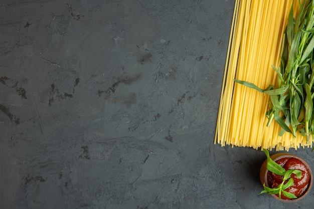 Vista dall'alto per spaghetti crudi e ketchup in una ciotola con copia spazio sul nero