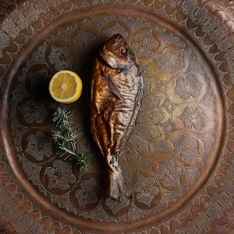 Vista dall'alto pesce affumicato con foglie di limone e rosmarino in vassoio di rame