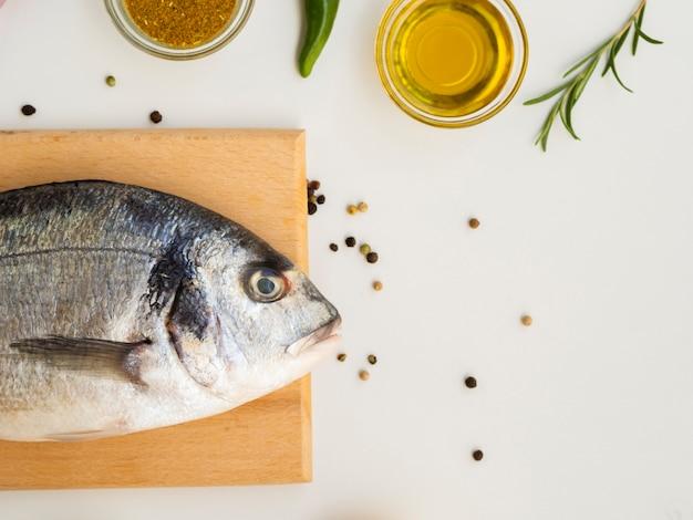 Vista dall'alto pesce fresco con condimenti ed erbe aromatiche