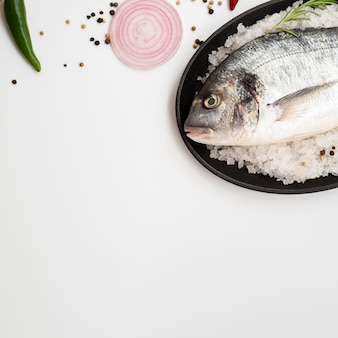 Vista dall'alto pesce fresco sul piatto con condimenti