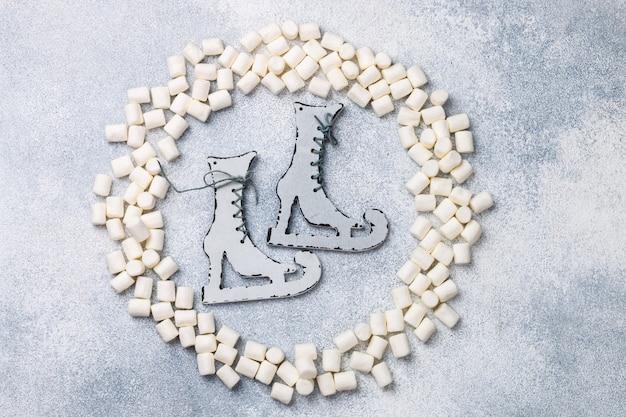 Vista dall'alto piatto di natale o capodanno con marshmallow e pattini giocattolo in legno rustico