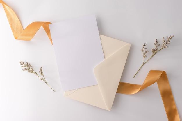 Vista dall'alto, piatto posare, carta di invito a nozze, buste, carte carte su sfondo bianco.