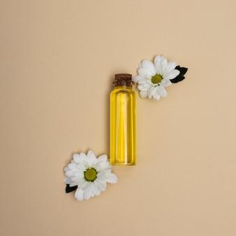 Vista dall'alto piccola bottiglia di olio con fiori