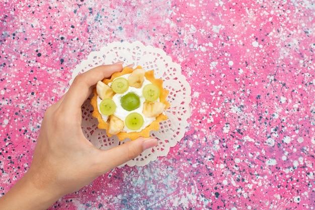 Vista dall'alto piccola deliziosa torta con crema e frutta a fette e femmina tenendo la torta sulla superficie colorata frutta dolce