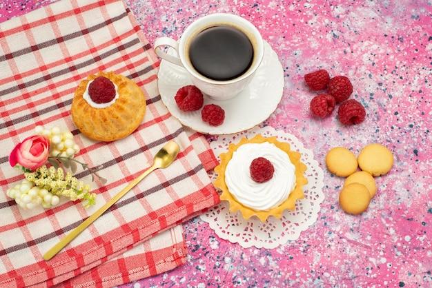 Vista dall'alto piccola torta con biscotti alla crema lamponi freschi insieme a una tazza di caffè sulla superficie colorata torta biscotto dolce colore del tè