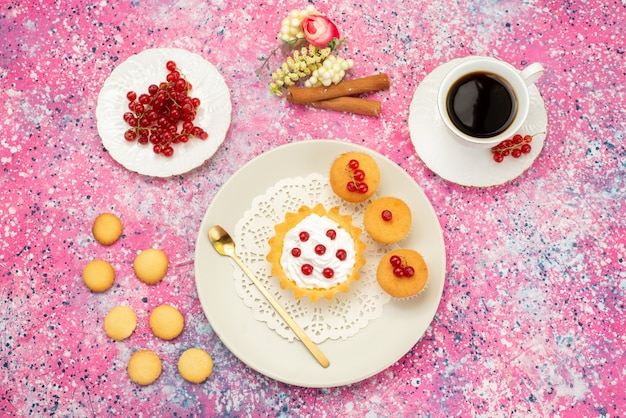 Vista dall'alto piccola torta con biscotti alla crema mirtilli rossi freschi con tazza di caffè e cannella sulla torta di superficie colorata dolce