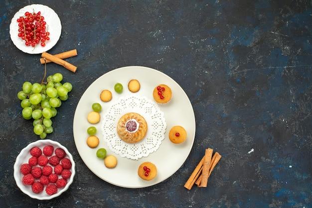 Vista dall'alto piccola torta con crema di biscotti e uva verde lamponi e mirtilli rossi sul dolce di frutta scrivania scuro