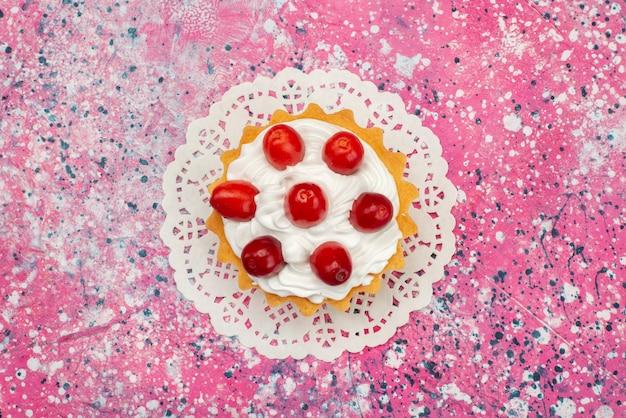 Vista dall'alto piccola torta con crema e frutta fresca sul colore del tè superficie colorata