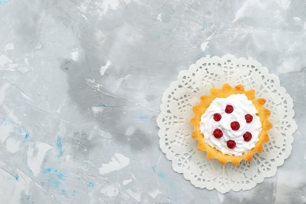 Vista dall'alto piccola torta cremosa con frutti rossi sulla superficie grigia dolce