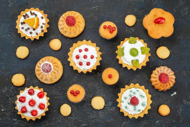 Vista dall'alto piccole deliziose torte con crema e frutta fresca sullo zucchero della torta di biscotti dolci superficie scura