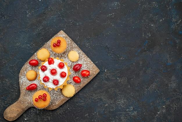 Vista dall'alto piccole torte buonissime con panna e frutta fresca sullo zucchero della torta di biscotti dolci superficie scura