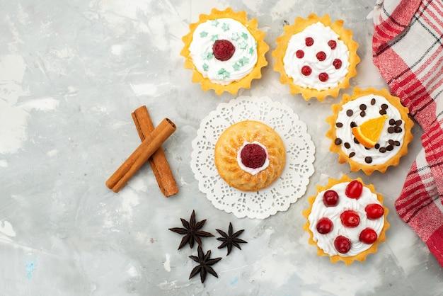 Vista dall'alto piccole torte d con crema di cannella e diversi frutti isolati sulla superficie leggera di zucchero dolce