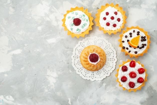 Vista dall'alto piccoli biscotti d con crema e diversi frutti isolati sulla superficie chiara torta di zucchero dolce