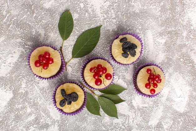 Vista dall'alto piccoli brownie al cioccolato con mirtilli rossi sullo sfondo chiaro torta biscotto zucchero dolce cuocere la pasta