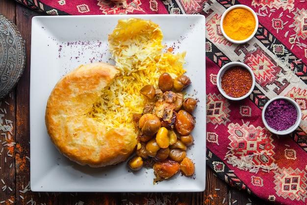 Vista dall'alto pilaf in una pita con castagne, albicocche secche, prugna ciliegia. piatto orientale tradizionale su una superficie di legno scuro orizzontale